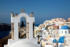 View of sea surface through traditional Greek white church arch with cross and bells in Oia village of Cyclades Island, Santorini,. Greece Royalty Free Stock Image