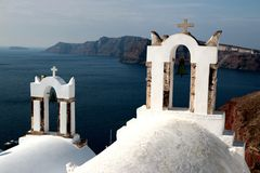 View of sea surface through traditional Greek white church arch with cross and bells in Oia village of Cyclades Island, Santorini,. Greece Royalty Free Stock Photo