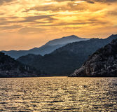 View from the sea to the mountainous coast with sunset. Stock Photography