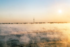 View from the sea to the TV tower in Tallinn at dawn in the fog. Royalty Free Stock Photo