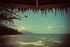 View of the sea under palm roof in retro colors Stock Photos