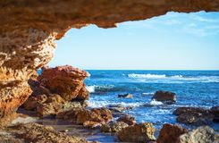 View of the sea waves and the sky from a stone cave royalty free stock photography