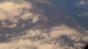 View Seacoast under Clouds from Airliner Window stock video footage