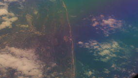 View Seacoast under Clouds from Airliner Window. Panorama of seacoast and azure sea under small clouds from airliner window stock video footage