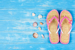 View of seashells and flip-flops lying on blue wooden background Stock Images