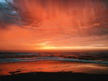 View of Seashore With Red and Yellow Clouds during Sunset Stock Photo