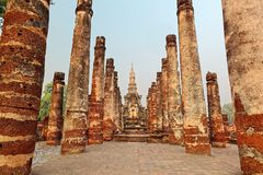 View of a seated Buddha statue among ruined columns in Wat Mahathat, an ancient Buddhist temple in Sukhothai Historical Park Royalty Free Stock Images