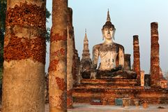 View of a seated Buddha statue among ruined columns in Wat Mahathat, an ancient Buddhist temple in Sukhothai Historical Park Stock Photography