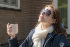 View of a woman with sunglasses sitting in her garden with her face accustomed to the first warm sun rays in early spring. while d stock photo