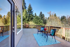 View of second floor deck finished with wooden railings. Also outdoor chairs accented with blue pillows paired with geometric pattern rug. Northwest, USA royalty free stock photos