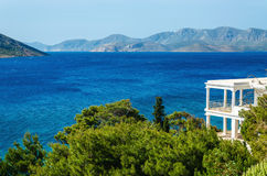 View on the see from typical Greek appartment with clear green t. Reens and amazing blue water and islands on horizon, Greece Stock Photo