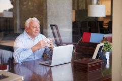 View Of Senior Man Using Laptop Through Window Royalty Free Stock Photo