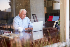 View Of Senior Man Using Laptop Through Window Royalty Free Stock Photos