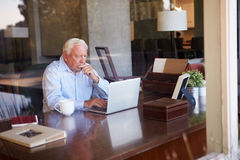 View Of Senior Man Using Laptop Through Window Royalty Free Stock Image