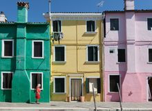 View of Senior woman with colorful dress walking across colorful facade in the island of Burano near Venice royalty free stock photos