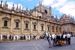 View of Seville cathedral with horse carriage. View of Seville cathedral and la giralda with cloudy sky Royalty Free Stock Image