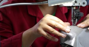 View of sewing machine for shoes. Woman s hand working at the factory with thread. 4K stock footage