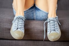 View of female legs in jeans shorts and blue sneakers on a gray couch. View of female legs in short jeans shorts and blue sneakers on a gray couch royalty free stock photo