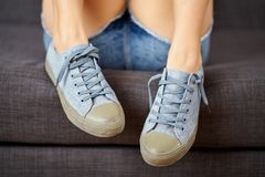 View of female legs in jeans shorts and blue sneakers on a gray couch. View of female legs in short jeans shorts and blue sneakers on a gray couch stock photography