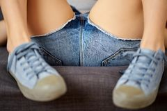 View of female legs in jeans shorts and blue sneakers on a gray couch. View of female legs in short jeans shorts and blue sneakers on a gray couch stock photos