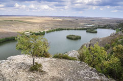 View from Sf.Ioan Casian's cave. Landscape view hill rock trees lake little isle high Dobrogea Romania clouds sky Royalty Free Stock Photography