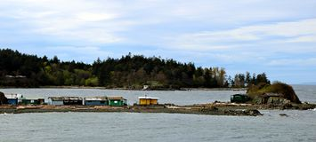 Little cabins on island in BC surrounded by Pacific Ocean. View of Shack Island from Pipers Lagoon on a cloudy BC day in Nanaimo stock photos