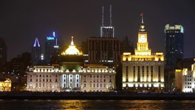 View Shanghai Bund from pudong at night,old style building & people silhouette. View Shanghai Bund from pudong at night,old europe style building neon lights stock footage