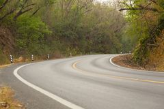 Sharp curve road in forest hill. View of sharp curve road in forest hill stock photos