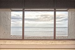 View through the shelter window in Llandudno, North Wales, United Kingdom. Artistic view of the sea through the framed window of the promenade shelter at Royalty Free Stock Image