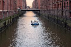 View at a ship in a canal of Elbe river in Hamburg`s Speicherstadt warehouse district, Germany. View at ship in a canal of Elbe river in Hamburg`s warehouse royalty free stock images