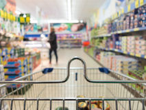 View from shopping cart trolley at supermarket shop. Retail. View from shopping cart trolley basket at supermarket self-service grocery shop. Retail. Blurred royalty free stock images