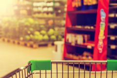 View from shopping trolley into abstract blurred supermarket ais Royalty Free Stock Image