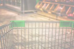 View from shopping trolley into abstract blurred supermarket ais Stock Photos