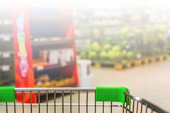 View from shopping trolley into abstract blurred supermarket ais Stock Photo