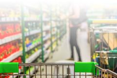 View from shopping trolley into abstract blurred supermarket ais Royalty Free Stock Images