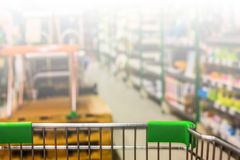 View from shopping trolley into abstract blurred supermarket ais Royalty Free Stock Photography