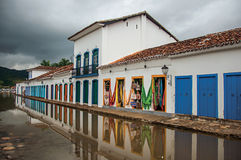 View of shops in old houses at alley with flooded stone walkway in Paraty. Royalty Free Stock Photo