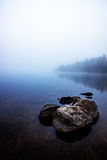 View from the shore of a fog covered lake Stock Images