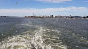 View of the shore and ocean from the stern of the ship.View of the waves following the ship in sunny weather.