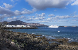 View from the shore of the ocean to the port of the village of P. Laya Blanca, Lanzarote Island, Canary Islands, Spain Stock Image