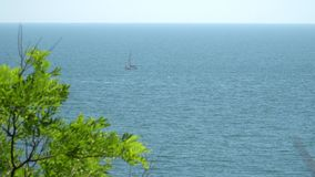 View from the shore to the boat under sail, which floats in the sea stock footage