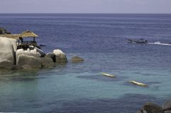 View of shores of Koh Tao island. (Thailand) : rocks, wood bungalow, crystal water, and long-tail boat Stock Photography
