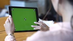 View from the shoulder of young woman in pink shirt sitting at the table and sliding on her tablet at the chroma key
