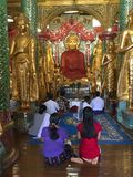 View of Shwedagon Pagoda, Yangon, Myanmar. View of a golden buddha and worshipers in the Shwedagon Pagoda. In the city of Yangon, Rangun, Myanmar royalty free stock photo