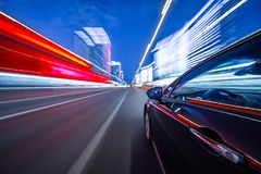 View from Side of Car moving in a night city. Blured road with lights with car on high speed. Concept rapid rhythm of a modern city stock photo