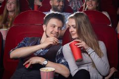 View from side of cute couple at cinema. stock images