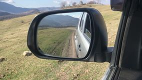 view in the side mirror, the car moves off-road in the Caucasus, slow motion stock video footage