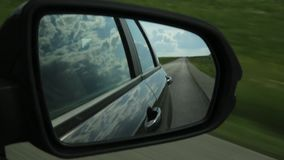 View of side mirror in a car, reflection of clouds and countryroad through the countryside on a summer day.  stock video footage