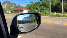 View of Side Mirror Reflection with Mountain and Highway. Travel by Car in Krabi, Thailand. HD. stock video footage