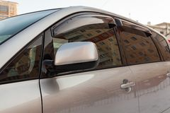 View of side rear view mirror and doors deflectors Toyota Ipsum last generation in silver color after cleaning before sale in a. Novosibirsk, Russia - 03.10.2019 royalty free stock image